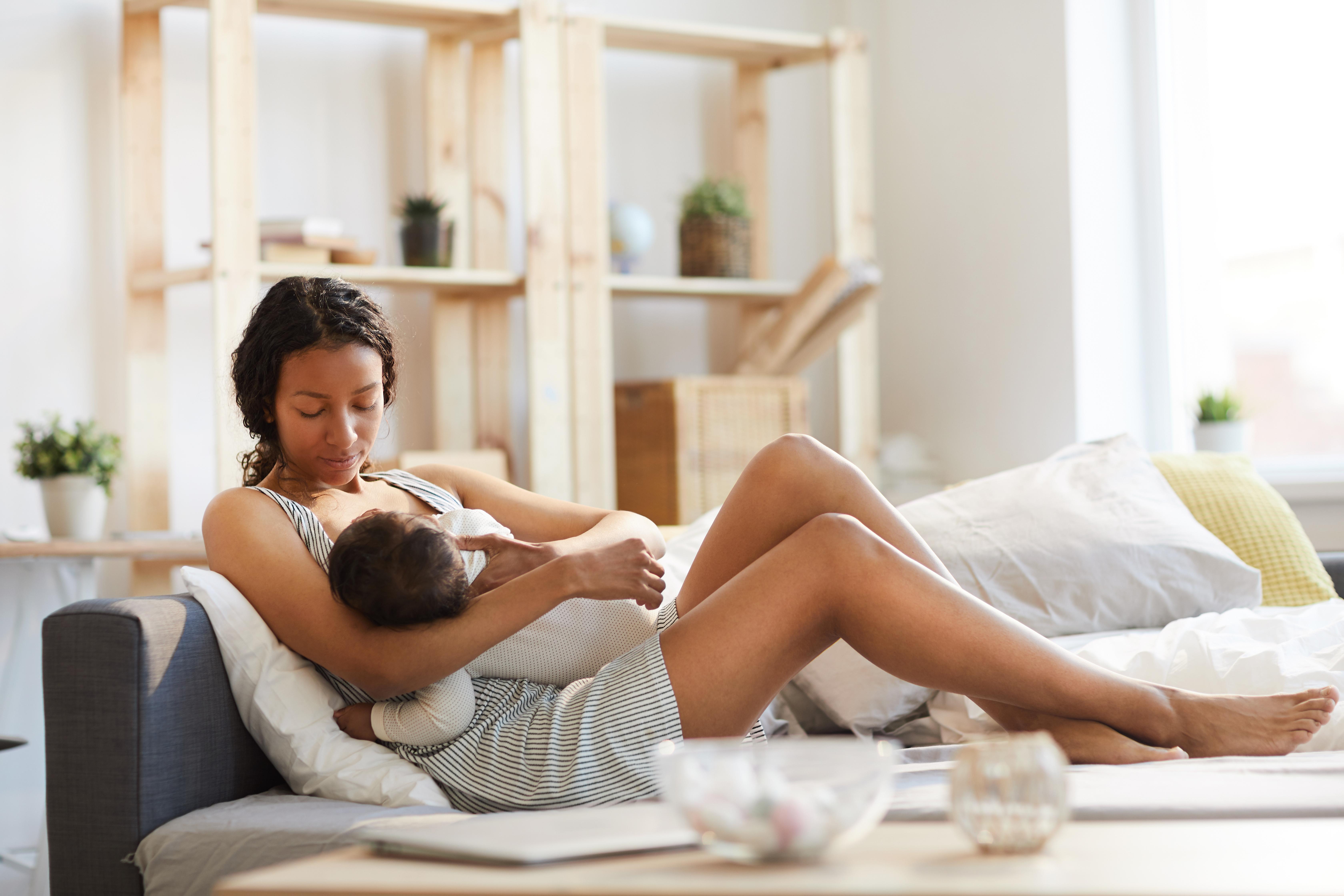 Mutter stillt ihr Baby auf der Couch